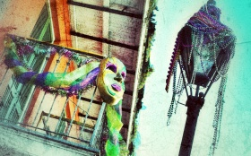 Beads decorate a light post while a Mardi Gras mask dresses up a balcony in the French Quarter in New Orleans.