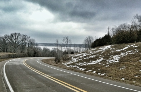 The Mississippi River can be seen in the distance as River Road makes a bend a few miles north of Keokuk, Iowa, on a gray March 2013 day.