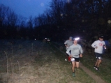 Several runners run down the trail in the first mile of the race before the sun comes up.