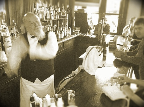 A bartender at Tujague's gives a vigorous and long shake to give a Ramos Gin Fizz its creamy, frothy texture.